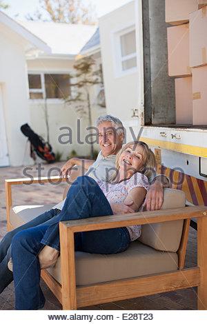 Couple sitting on sofa beside moving van - Stock Photo
