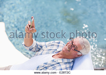Senior man using cell phone at poolside - Stock Photo