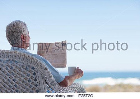 Senior man with coffee and newspaper on beach patio - Stock Photo