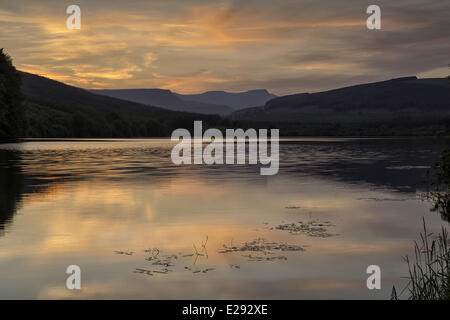 View of reservoir and distant hills at sunset, Penyfan, Taf Fechan Reservoir, Brecon Beacons N.P., Merthyr Tydfil, Wales, July Stock Photo