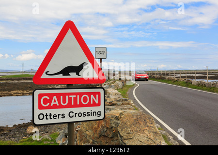 Caution Otters Crossing red triangle road sign by causeway from Benbecula to North Uist Outer Hebrides Western Isles - Stock Photo