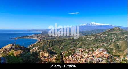 View of Mount Etna covered of snow, city of Taormina and coastline - Stock Photo