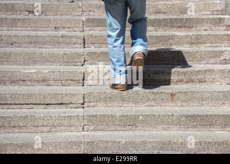 Man climbs on a concrete stairs - Stock Photo