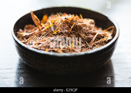 Rooibos tea leaves in a bowl - Stock Photo
