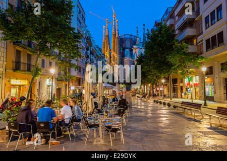 outdoor cafe by night in avinguda de gaudi with sagrada familia church behind barcelona