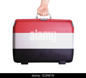 Used plastic suitcase with stains and scratches, printed with flag, Yemen - Stock Photo