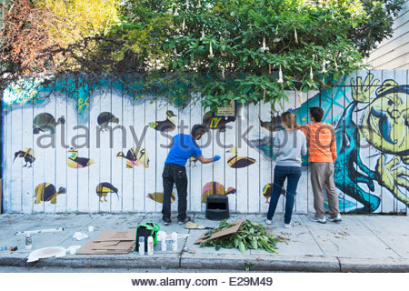 Muralists Spray Painting Graffiti Art on Lucky Alley Wall in Mission District, San Francisco, California - Stock Photo