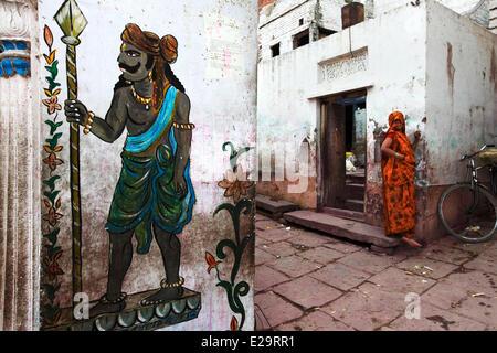 India, Uttar Pradesh State, Varanasi, woman on the doorstep - Stock Photo