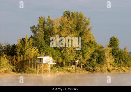 France, Gironde, Dordogne, hut of fishing called carrelet, raised by the sun on the Dordogne and morning mists - Stock Photo