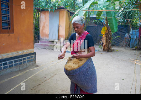 India, Kerala state, Allepey, backwaters, woman of a village preparing the rope - Stock Photo