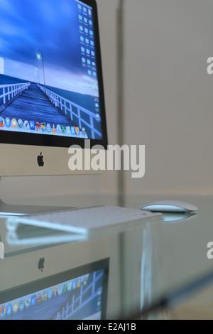 Apple iMac computer on a glass desk - Stock Photo