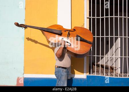 Cuba, Sancti Spiritus Province, Trinidad de Cuba, listed as World Heritage by UNESCO, man carrying a boublebass - Stock Photo