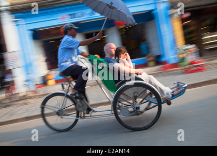 Tourists riding in cyclo, Hoi An (UNESCO World Heritage Site), Quang Ham, Vietnam - Stock Photo