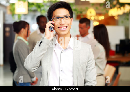 Portrait of a smiling businessman talking on the smartphone in front of colleagues - Stock Photo