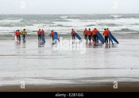 Ireland, County Kerry, Inch, surfers walking on the beach in bad weather - Stock Photo