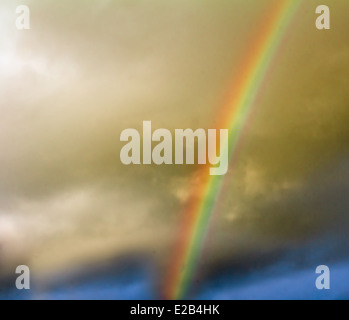 The sky with dark cumulonimbus clouds and a rainbow against clouds. - Stock Photo
