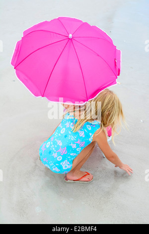 Little blond girl at the beach with a pink umbrella plays in sand - Stock Photo