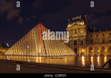 Louvre Museum and the Pyramid in Paris, France, at night illumination - Stock Photo