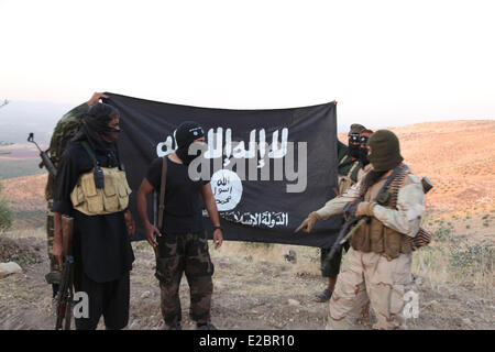 Oct 17, 2013 - Aleppo, Syria - ISIS fighters holding the Al-Qaeda flag with 'Islamic State of Iraq and the Levant' - Stock Photo