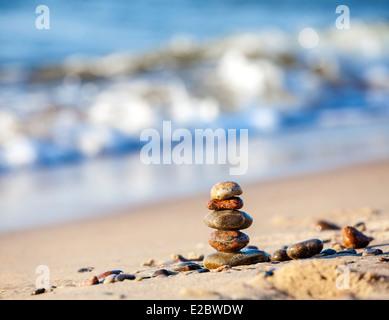 Stones pyramid on sand symbolizing zen, harmony, balance, blue ocean in the background . - Stock Photo