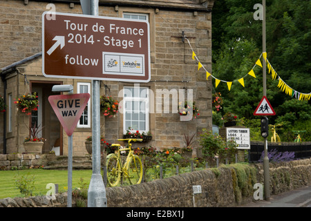 Brown tourist road sign, decorative bunting & yellow bikes on display in garden - before Le Tour de France, Addingham - Stock Photo