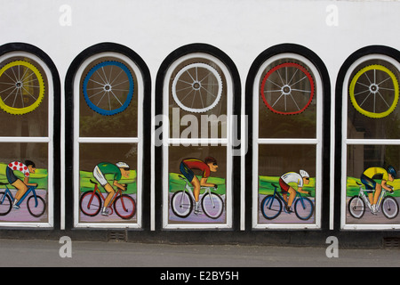 Attractive, artistic, painted series of windows celebrating the Tour de France (bike riders & wheels) - shop front, - Stock Photo