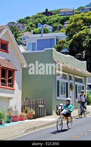 cyclists ride down hill  into Sausalito from San Francisco - Stock Photo