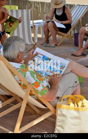 France, Herault, Valras Plage, man sat in a deckchair and reading one comic strip - Stock Photo