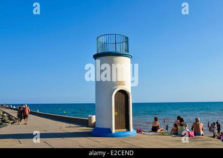 France, Herault, Valras Plage, small lighthouse on pier in homage to disappeared fishermen, vacationers taking sun - Stock Photo