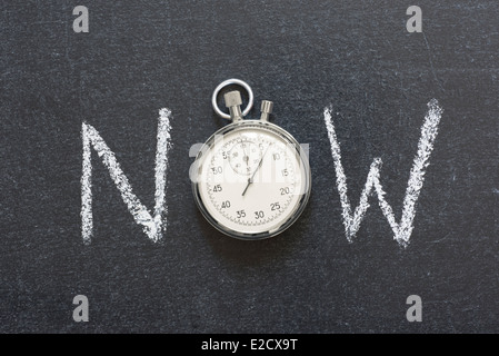 now concept handwritten on chalkboard with vintage precise stopwatch used instead of O - Stock Photo