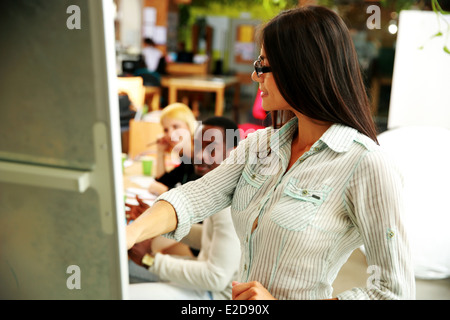 Happy businesswoman presenting something on a meeting - Stock Photo