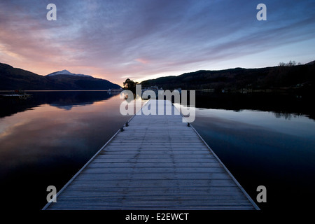 The pre sunrise colours on a still loch Lomond with the jetty at inveruglus leading into the loch - Stock Photo