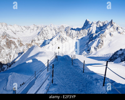 Roped path route to Vallee Blanche with skiers descending arête on Aiguille du Midi. Chamonix-Mont-Blanc Rhone-Alpes - Stock Photo