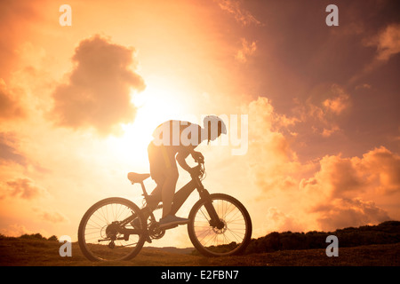The silhouette of mountain bicycle rider on the hill - Stock Photo
