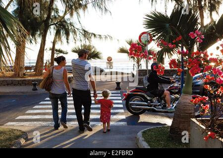 France Reunion island (French overseas department) Saint Leu urban landscape horizontal view of a family crossing - Stock Photo