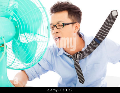 Young man cooling face under wind of fan - Stock Photo