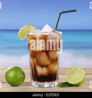 Cola or Cuba Libre cocktail drink in glass with ice cubes on the beach - Stock Photo