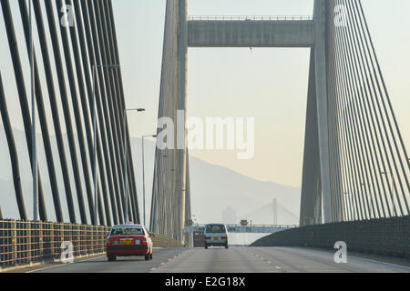 China Hong Kong Lantau Island red taxi on a highway exceeding the suspension bridge of Tsing Ma - Stock Photo