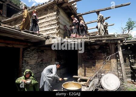 Pakistan Khyber Pakhtunkhwa Kalash valleys Bumburet valley Krakal village Kalash taking in a huge cooking-pot of - Stock Photo