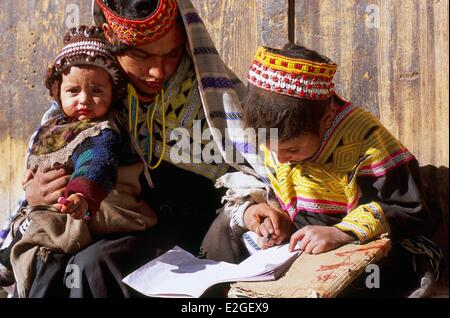 Pakistan Khyber Pakhtunkhwa Kalash valleys Bumburet valley little girl doing her school duties to helped of her - Stock Photo