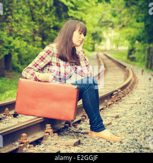 young teenager sad girl with suitcase sitting on the rails - Stock Photo
