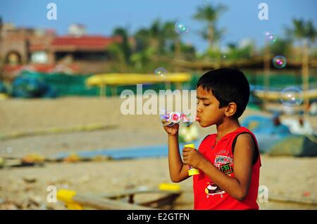 India Odisha state Puri little boy blowing bubbles on beach - Stock Photo