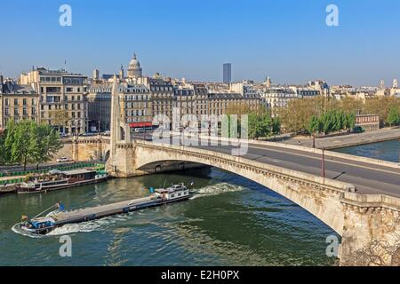 France Paris banks of Seine river listed as World Heritage by UNESCO river Seine and a boat with Pont de Tournelle - Stock Photo
