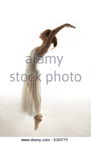 teen ballerina in a white tutu standing on point on a white seamless background in silhouette stretching in profile. - Stock Photo