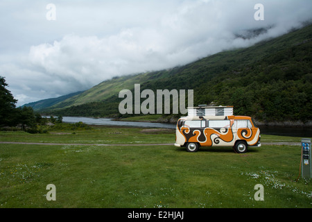 A Volkswagen camper van parked at a lochside campsite in Scotland. - Stock Photo