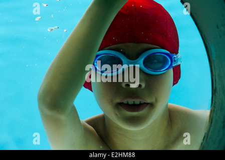 Boy underwater, looking through porthole, portrait - Stock Photo