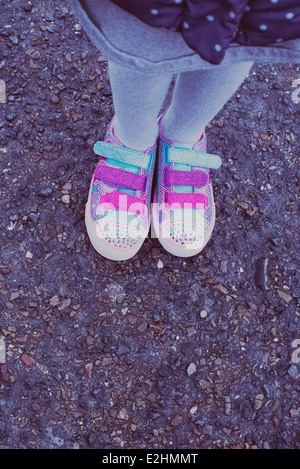 Girl wearing colorful sneakers, low section - Stock Photo