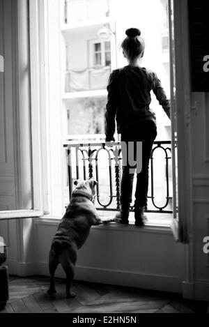 Girl standing on windowsill with pet dog, both looking out - Stock Photo