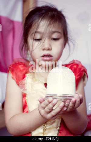 Little girl looking at snow globe - Stock Photo