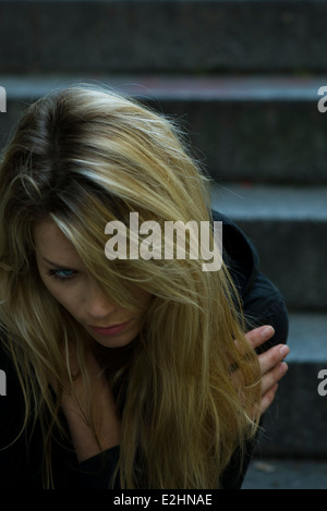 Woman sitting alone on steps - Stock Photo
